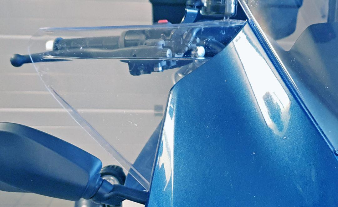 Gerhards egentillverkade handtagsskydd fästs med befintliga skruvar som håller ihop kåpa och hållare till vindrutan.