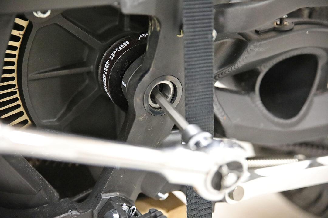 Bulten som håller framdrevet på plats är en torx T50 som enklast nås genom hålet i svingens infästning. En kort ½-tumshylsa får dock inte plats utan det krävs en lite längre hylsa för att nå igenom hålet.