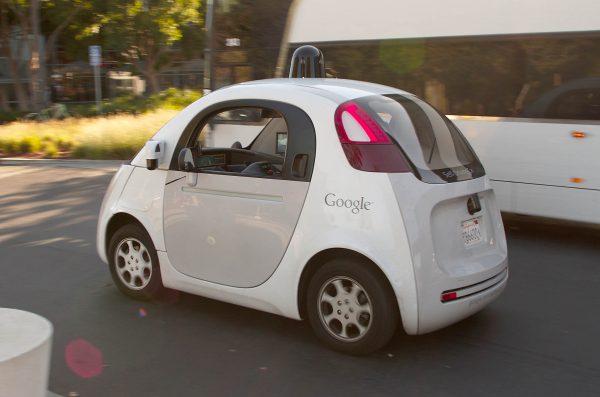 Googles självkörande bil kör om en buss vid Googles huvudkontor i Mountain View, Kalifornien, USA. Foto: Michael Shick, CC-SA 4.0.